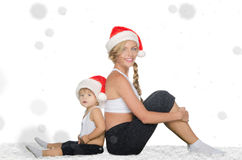 Woman with child sitting on snow in Santa hats Stock Image