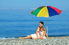 Woman and child sitting under an umbrella. The woman and small girl sitting under an umbrella on the beach Royalty Free Stock Photo