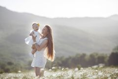 Beautiful mother and her daughter playing in spring flower field Royalty Free Stock Photos