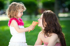 Woman and child in spring park. Woman and child eating ice-cream in spring park Royalty Free Stock Image