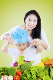 Woman and child stirring salad. Young Asian women and her son stirring a bowl of vegetables salad, shot with green screen background Royalty Free Stock Photography