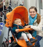 Woman with child in stroller at metro. Smiling women with child in stroller at metro train stock photography