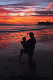 Woman with child takes picture of purple and orange sunset looking towards Anacapa Island, Ventura, California, USA royalty free stock photography