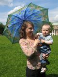 Woman with a child and umbrella. Young woman with a little child (boy) in hands and umbrella in the park Stock Image