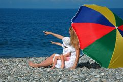 Woman with child under umbrella on beach Stock Photos
