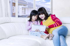Woman and child use tablet on couch Stock Image