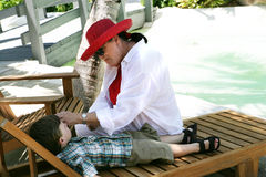 Woman and child on vacation. Woman and young boy in a beach setting, boy on lounge chair, caucasian/white Stock Images