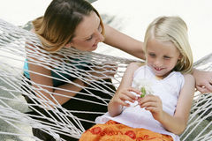 Woman and child on vacation. Young girl in a hammock with adult female looking on, caucasian/white Royalty Free Stock Photography