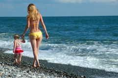 Woman and child walk on the beach Royalty Free Stock Photo