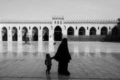 A woman and child walk through the courtyard of the al-Hakim Mosque in Cairo royalty free stock photography