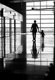 Woman and child walking. A silhouette of a woman and a child walking holding hands in an airport Stock Photos