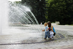 Woman and child walking around splashing fontain in the center o Royalty Free Stock Photos