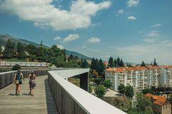 Woman and child walking on footbridge over valley with building. Covilha, Portugal - July 11, 2018. Woman and child walking on footbridge over valley with royalty free stock image