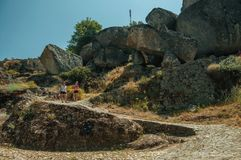 Woman and child walking by a path with rocks in Monsanto. Monsanto, Portugal - July 13, 2018. Woman and child walking by a cobblestone path with rocks and dry stock photo