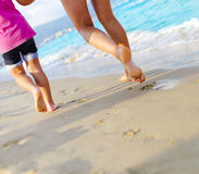 Woman and child walking through sand Stock Images