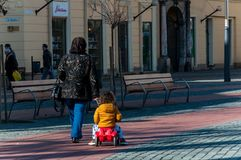 Woman and child walking on the street. TIMISOARA, ROMANIA - MARCH 15, 2018: Grandmother pulling her child with a tricycle. Walking on the street, in the city royalty free stock photo