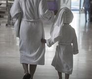 A woman with a child in white bathrobes walking in a spa center royalty free stock photo