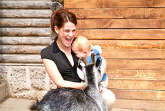 Woman with child who pat the goat at the zoo Royalty Free Stock Photography