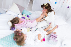 Woman and children on bed Royalty Free Stock Images