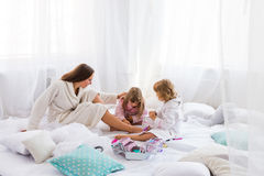 Woman and children on bed Stock Images