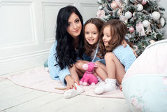 Woman with children blue knit cardigan in the bed near Christmas tree. The black-haired women with two girls, three and five years in the bedroom of gentle blue Stock Image