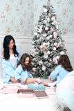 Woman with children blue knit cardigan in the bed near Christmas tree. The black-haired women with two girls, three and five years in the bedroom of gentle blue Royalty Free Stock Images