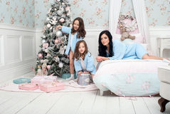 Woman with children blue knit cardigan in the bed near Christmas tree. The black-haired women with two girls, three and five years in the bedroom of gentle blue Stock Photo