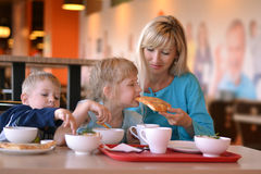The woman and children in cafe. The young women and two children eat in cafe Royalty Free Stock Photography