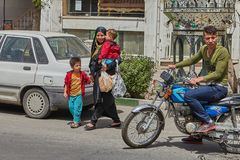 Woman with children crossing road in front of motorbike, Iran. Kashan, Iran - April 27, 2017: Muslim woman wearing a black chador, crosses the carriageway of Stock Photos