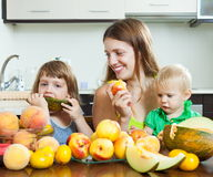 Woman with children eating fruits Stock Photo