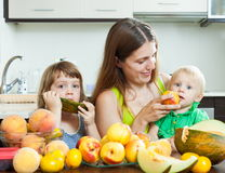Woman with children eating melon Royalty Free Stock Image