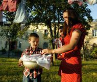 Woman with children in garden hanging laundry Royalty Free Stock Photos