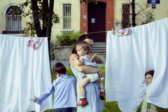 Woman with children in garden hanging laundry Stock Images