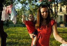 Woman with children in garden hanging laundry outside Stock Photo