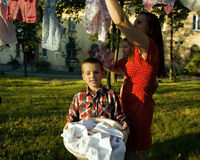 Woman with children in garden hanging laundry outside Royalty Free Stock Image