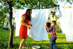 Woman with children in garden hanging laundry outside, playing with cute baby girl toddler, lifestyle people concept. Close up Stock Photo