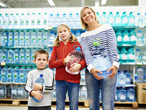 Woman with children is holding bottle drinking water in shop Royalty Free Stock Photo