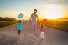 Woman with children jumped on a rural road in the light of a sun stock photos
