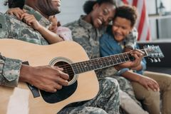 Woman and children listening to father in camouflage clothes. Playing guitar royalty free stock photo