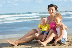 Woman with children playing on the beach Stock Photography