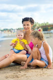Woman with children playing on the beach Royalty Free Stock Images