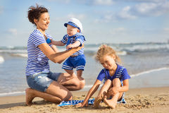 Woman with children playing on the beach Royalty Free Stock Image
