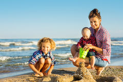 Woman with children playing on the beach Stock Image