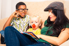 Woman and children reading book. Young happy women with children reading book and relaxing on sofa Stock Photos