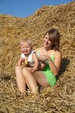 Woman with children resting on a haystack Stock Photography