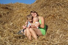 Woman with children resting on a haystack Royalty Free Stock Photography