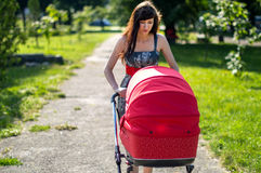 The woman with a children's carriage on walk on alley Royalty Free Stock Images