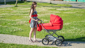 The woman with a children's carriage on walk on alley Stock Photography