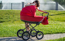 The woman with a children's carriage on walk on alley Royalty Free Stock Photo