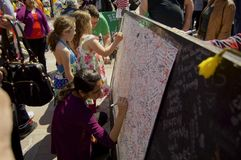 Woman and children sign card. Boston, Massachusetts USA - April 2013 - Visitors signing large white card with hundreds of signatures covering it at Boston Royalty Free Stock Image